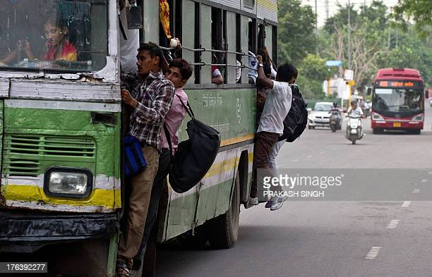 Indian commuters hang on to the doors of a crowded city bus in New Delhi on August 12 2013 India has one of the world's highest number of road deaths...