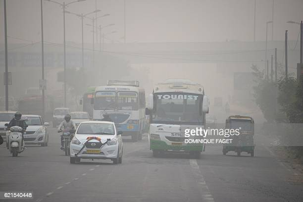 Indian commuters journey along a major road as heavy smog covers New Delhi on November 7 2016 Schools in the Indian capital will be closed for the...