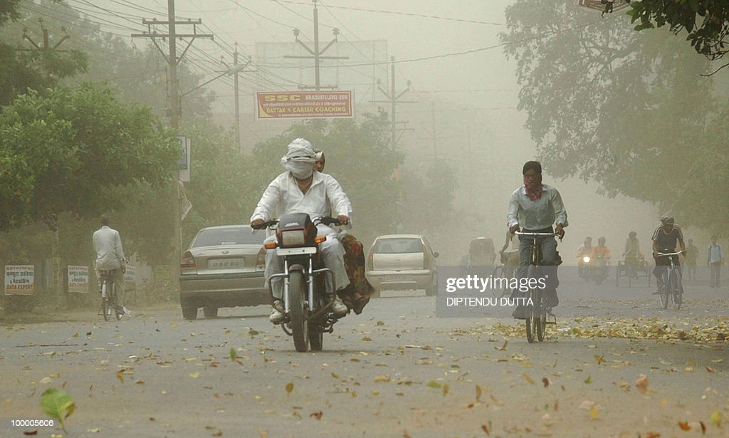 Indian commuters journey through a dust storm in Allahabad on May 20, 2010. Heatwave conditions continue to prevail over northern India with temperatures rising above the 45 degrees Celsius mark. Isolated dust storms are forecast throughout the region. AFP PHOTO/Diptendu DUTTA