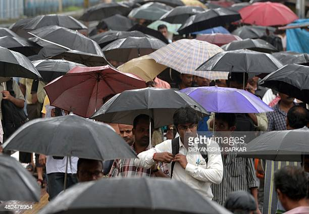 Indian commuters leave a railway station under heavy rain from Cyclone Komen in Kolkata on July 31 2015 The cyclone made landfall in Bangladesh as it...