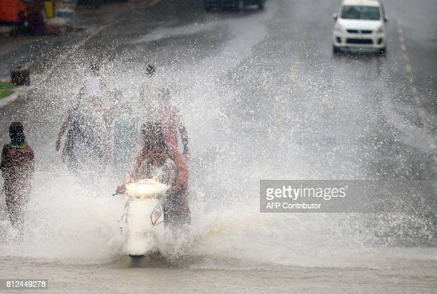 Indian commuters make their way on a waterlogged street after heavy rain in Allahabad on July 11 2017 / AFP PHOTO / SANJAY KANOJIA