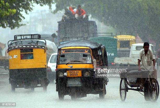 Indian commuters make their way through a heavy downpour of rain in Amritsar on July 5, 2008. The south-western monsoon is advancing across the...