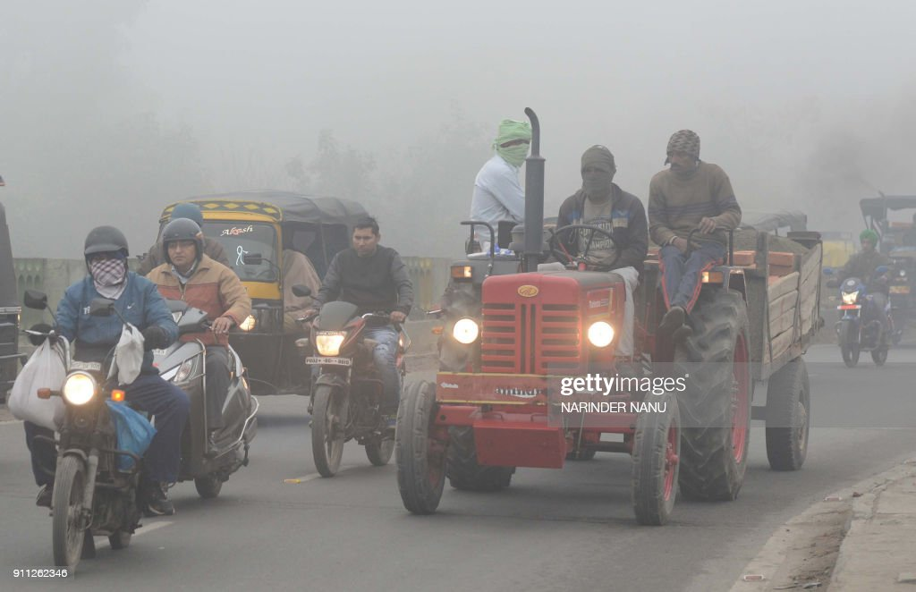 Indian commuters make their way through heavy fog and air pollution in Amritsar on January 28 2018 / AFP PHOTO / NARINDER NANU