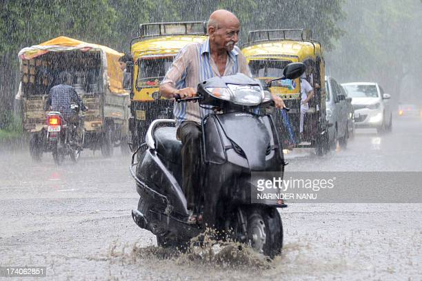 Indian commuters make their way through heavy rains in Amritsar on July 20 2013 The monsoon season which runs from June to September accounts for...