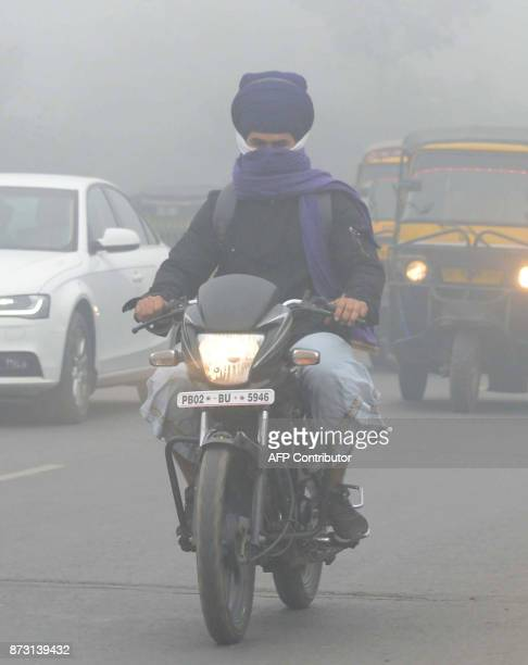 Indian commuters make their way through heavy smog in Amritsar on November 12 2017 Large swathes of north India and Pakistan see a spike in pollution...