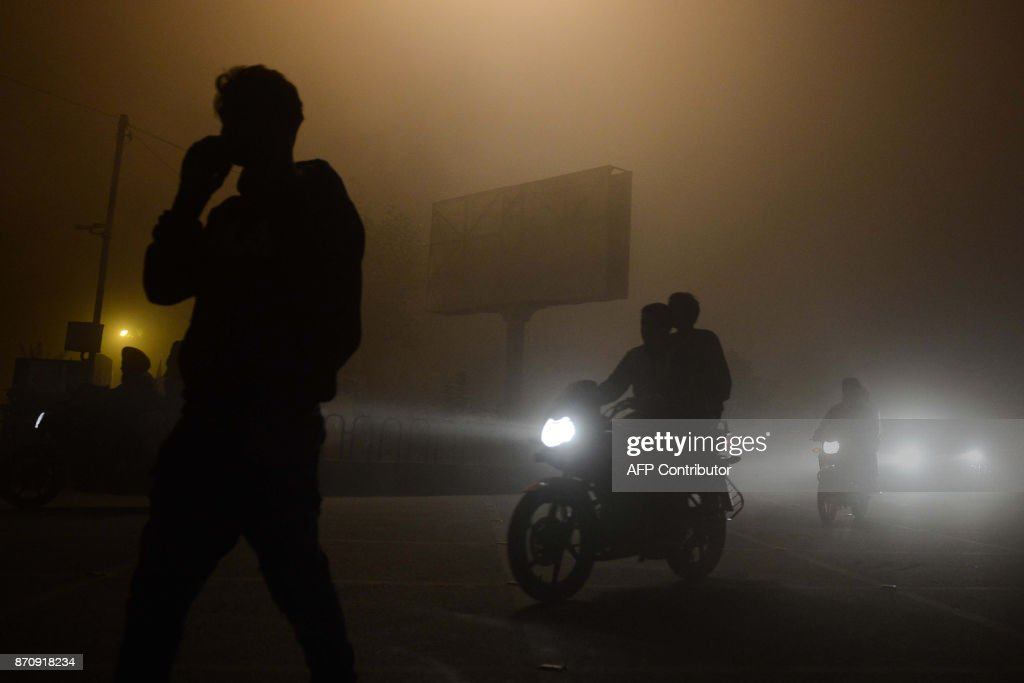 Indian commuters make their way through thick fog in Amritsar on November 6 2017 / AFP PHOTO / NARINDER NANU