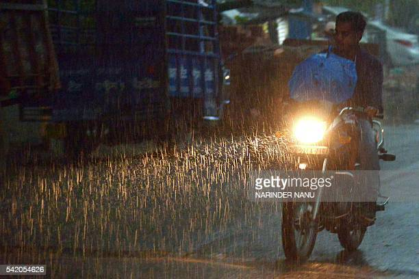 Indian commuters make their way through through the rain in Amritsar on June 22 2016 At least 67 people have been killed by lightning in India over...