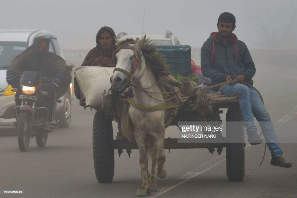 Indian commuters makes their way through dense fog on the outskirts of Amritsar on February 6 2017 / AFP / NARINDER NANU