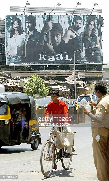 Indian commuters pass a billboard advertising the film 'Kaal' outside a cinema hall in south Bombay 29 April 2005 Kaal is the story of a young couple...