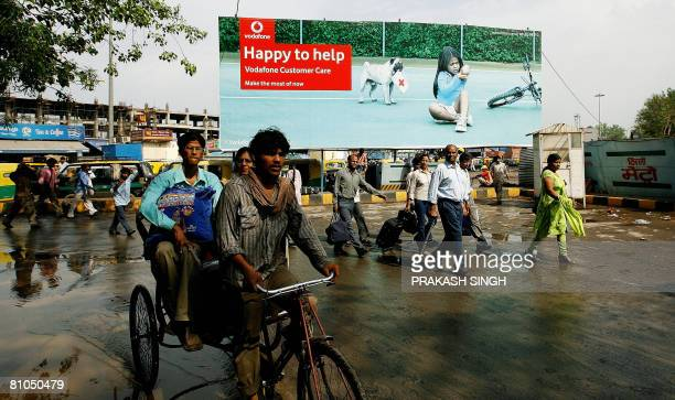 Indian commuters pass by a billboard of British mobile giant Vodafone in New Delhi on May 11 2008 The Indian unit of British mobile giant has been...