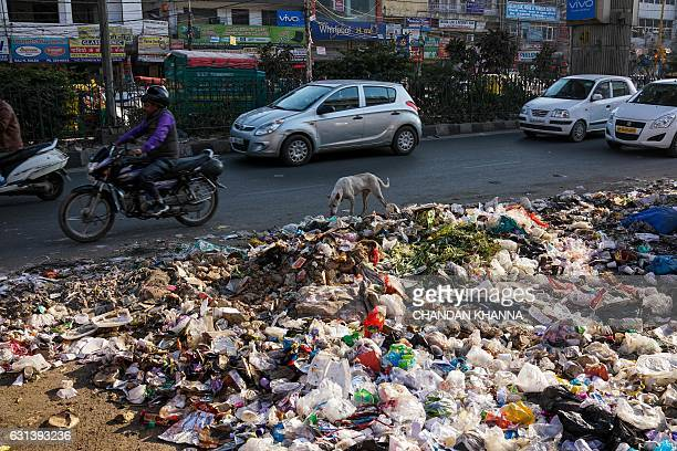 Indian commuters pass by a roadside garbage dump in New Delhi on January 10 2017 The national capital has been reeling under tonnes of garbage after...