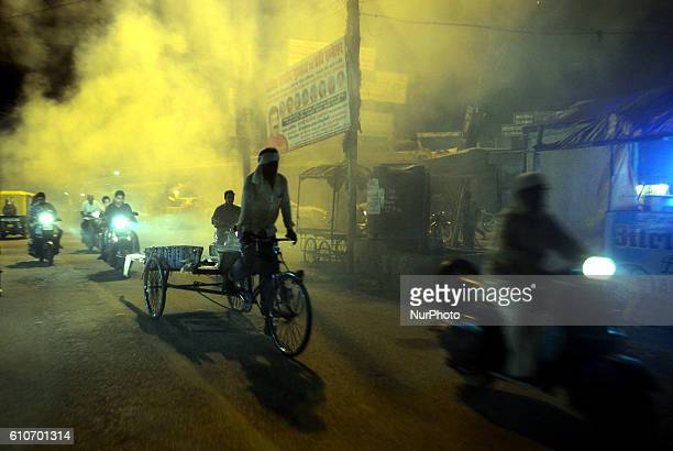 Indian commuters pass through smoke from fumigation in a busy old street of Allahabad on September 27201621 people died of dengue in last 3 weeks...