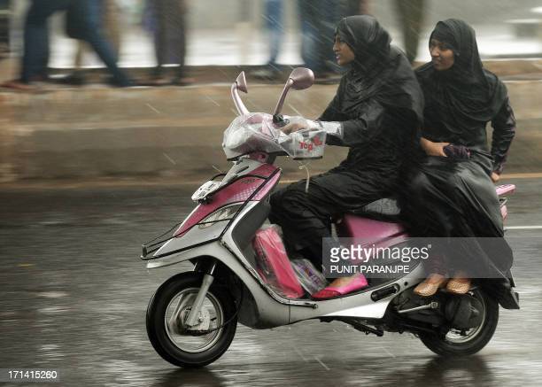 Indian commuters ride a scooter during a heavy rain shower in Mumbai on June 24 2013 The monsoon which covers the subcontinent from June to September...