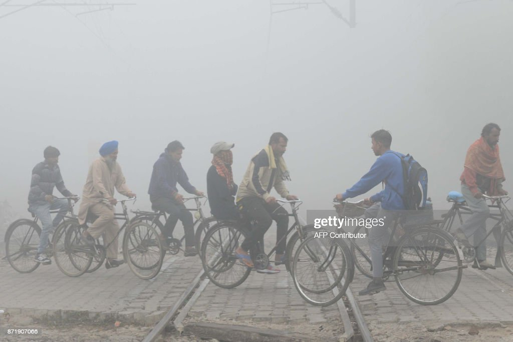 Indian commuters ride over tracks at a railway crossing amid heavy smog in Amritsar on November 9 2017 Schools closed across large swathes of north...