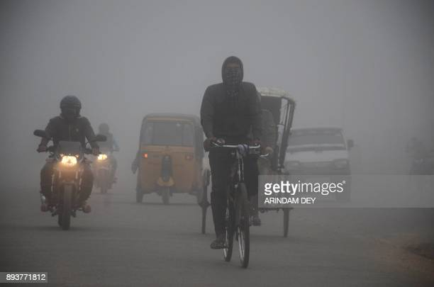 Indian commuters travel during a foggy morning in Agartala the capital of northeastern state of Tripura on December 16 2017 / AFP PHOTO / Arindam DEY