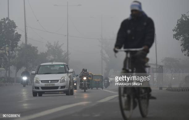 Indian commuters travel on a cold foggy morning in New Delhi on January 4 2018 / AFP PHOTO / Prakash SINGH