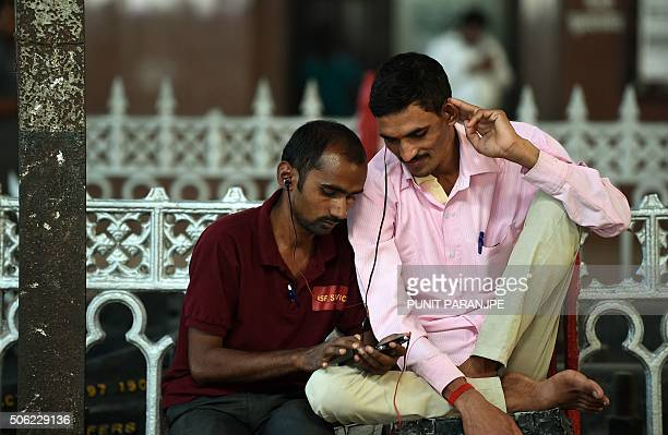 Indian commuters use their smartphones following the introduction of a new free WiFi Internet service in Mumbai's central railway station on January...