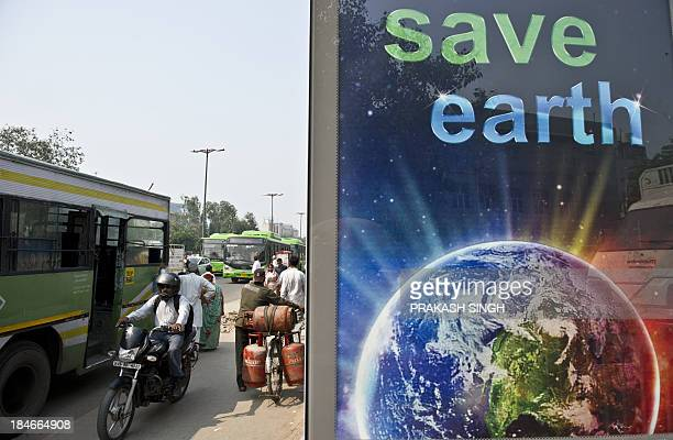 Indian commuters wait at a bus stop with a billboard advocating environmental conservation in New Delhi on October 15 2013 India plans to spend 110...