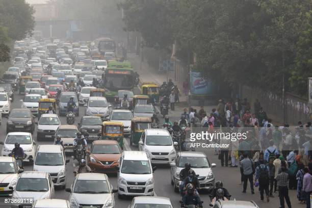 Indian commuters wait for a bus next to heavy traffic on a smoggy morning in New Delhi on November 14 2017 Doctors declared a public health emergency...