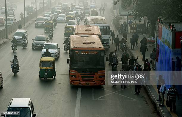 Indian commuters wait for their ride at a bus stop where air purifiers have been installed in New Delhi on December 27 2016 New Delhi's air quality...