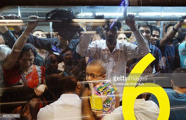 Indian commuters wait inside a carriage of the metro train at a station in New Delhi on July 11 on the occasion of World Population Day World...