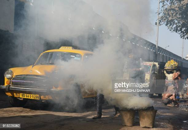 Indian commuters walk past as smoke comes out of traditional Indial coal 'chulahs' kept on the side of a busy road in Kolkata on February 7 2018 /...