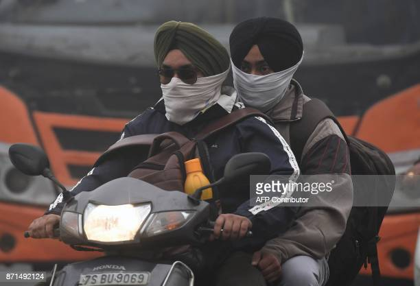 Indian commuters wear masks amid heavy smog in New Delhi on November 8 2017 Delhi shut all primary schools on November 8 as pollution levels hit...