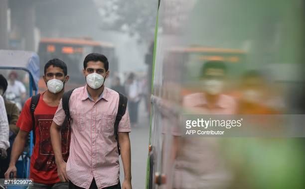 TOPSHOT Indian commuters wear masks as they walk along a road amid heavy smog in New Delhi on November 9 2017 Rickshaw driver Sanjay can only afford...