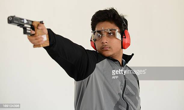 Indian competition shooter Rushiraj Atul Barot aims his pistol during a practise at the Ahmedabad Military and Rifle Training Association/ Rifle Club...