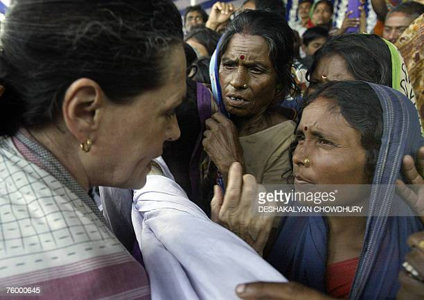 Indian Congress Party leader Sonia Gandhi speaks with flood affected villagers at a camp in Samastipur some 160 kms north of Patna 07 August 2007...