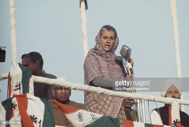 Indian Congress Party politician Indira Gandhi stands on a podium and speaks through a microphone as she addresses an election campaign meeting prior...