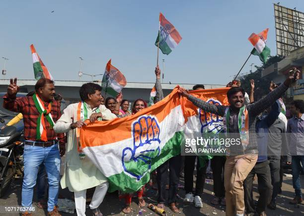 Indian Congress party supporters hold a Congress party flag as they celebrate in Ahmedabad on December 11 2018 India's ruling party looked set to...