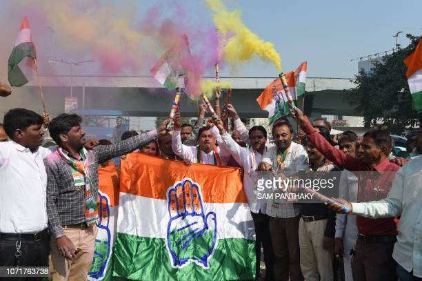 Indian Congress party supporters hold Congress party flag as they celebrate in Ahmedabad on December 11 2018 India's ruling party looked set to lose...