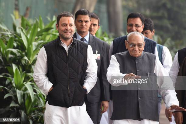 Indian Congress Party Vice President Rahul Gandhi walks with party leader Motilal Vora as he arrives to file his nomination papers for the post of...