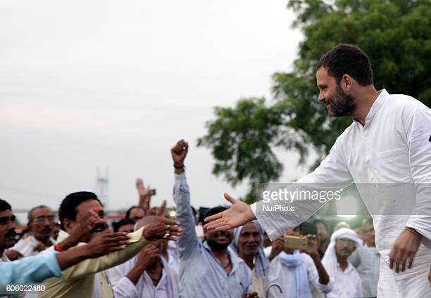Indian Congress party's vice president and leader Rahul Gandhi shakes hands with local party workers during a public meeting popularly known as Khaat...