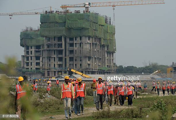 Indian construction labourers walk to their shelter during a shift change at a housing project construction site in Kolkata on March 1 2016 The...