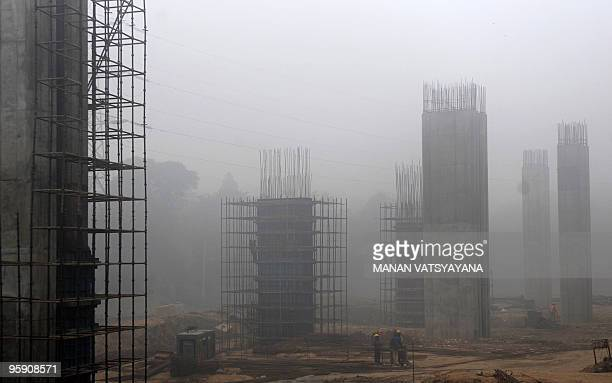 Indian construction workers labour at an underconstruction site on a foggy morning in New Delhi on January 21 2010 Winter fog during the last days...