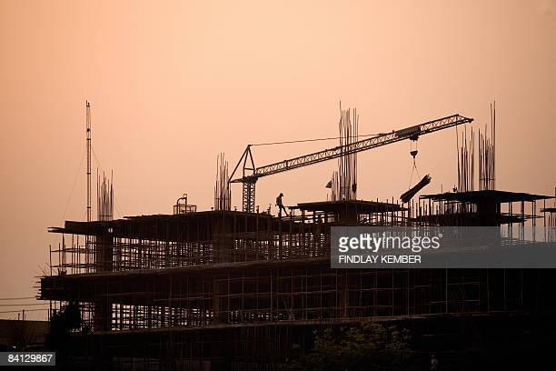 Indian construction workers labour on a new building in Gurgaon on the outskirts of New Delhi on October 31, 2008. Delhi, the capital of India, is...