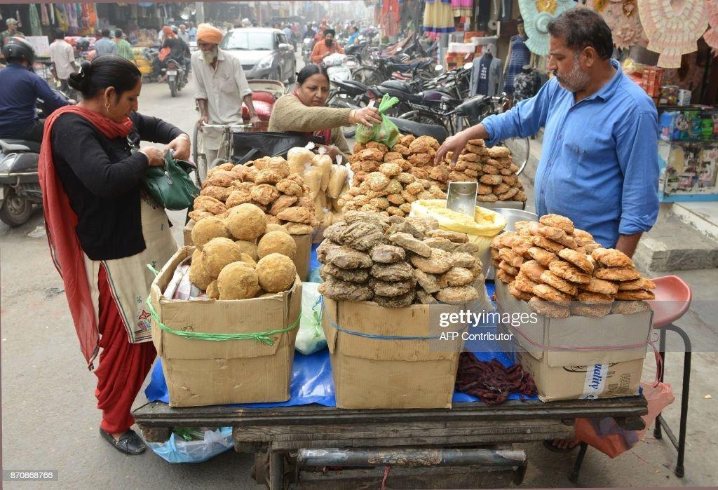 Indian costumers buy jaggery at a road side food cart in Amritsar on November 6 2017 / AFP PHOTO / NARINDER NANU