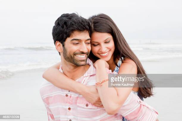 Indian couple hugging on beach