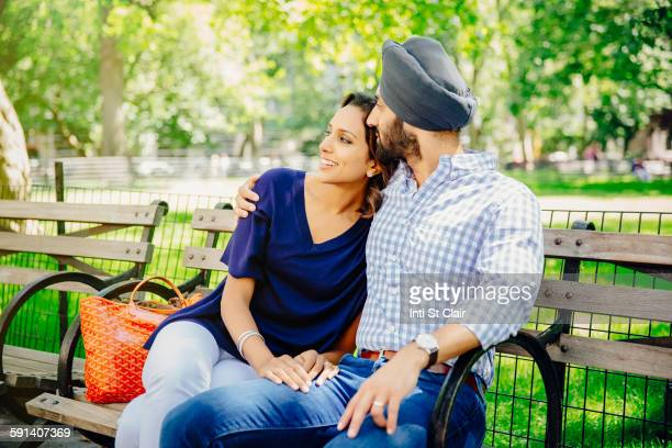Indian couple hugging on bench in urban park