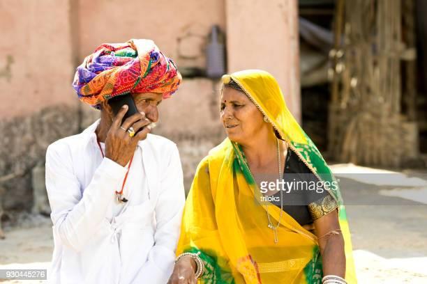 casal indiano em roupas tradicionais, usando telefone celular - artigo de vestuário para cabeça - fotografias e filmes do acervo
