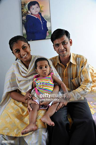 Indian couple Jayesh and Rekha Dua pose with their recently adopted girl Kejal at their residence in Ahmedabad on the eve of Mother's day on May 9...