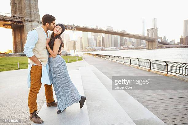Indian couple kissing by bridge, New York, New York, United States
