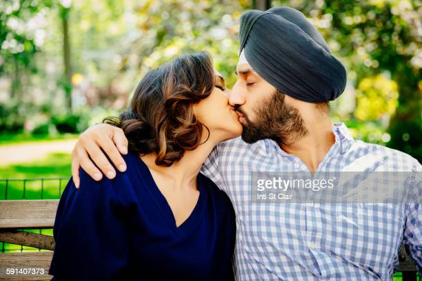 indian couple kissing on bench in urban park - indian couples stock pictures, royalty-free photos & images