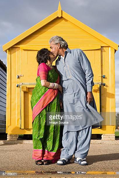 Indian couple kissing outside beach hut