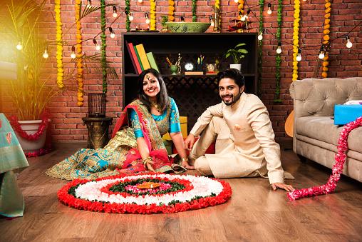Indian couple making flower Rangoli on Diwali or Onam Festival, taking selfie or holding sweets 1178984568