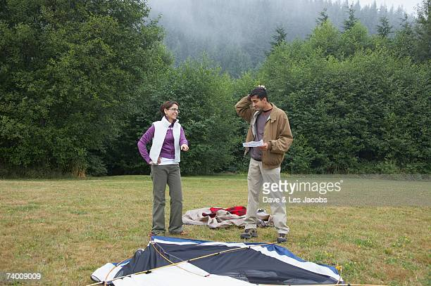 indian couple putting up tent - instructions stock pictures, royalty-free photos & images