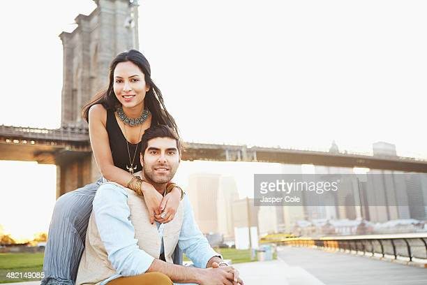 Indian couple smiling by bridge, New York, New York, United States
