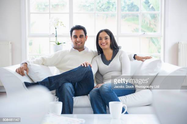 Indian couple smiling on sofa